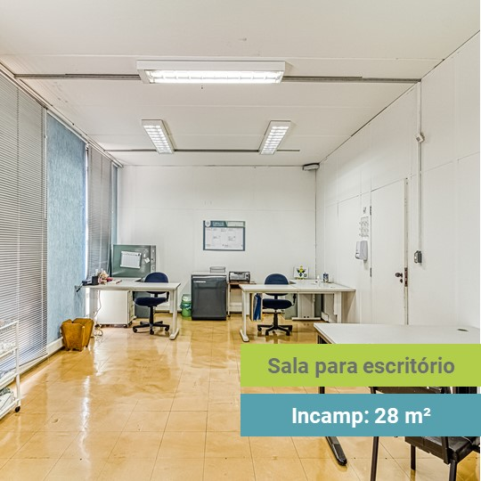 Foto de uma sala vazia, apenas com três mesas e três cadeiras