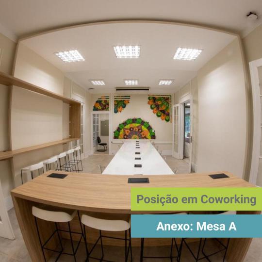 A foto é de uma sala para coworking com uma mesa extensa ao centro. As paredes são brancas e, na parede do fundo, há um desenho colorido. Na parede à esquerda há banquetas com um suporte para apoiar objetos.