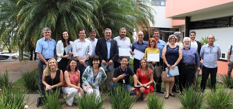 Foto posada de mentores em pé e agachados com certificados de mentorias