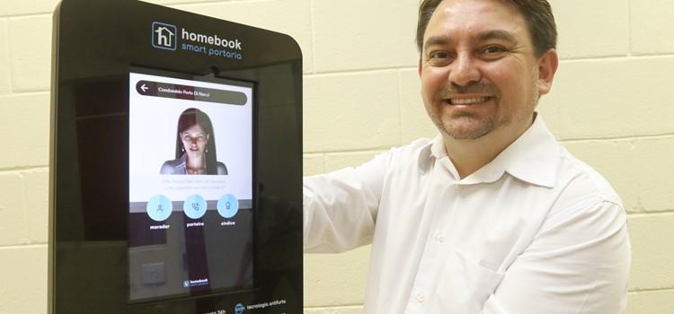 Alcino Vilela está segurando o dispositivo da portaria inteligente com o avatar do porteiro robô