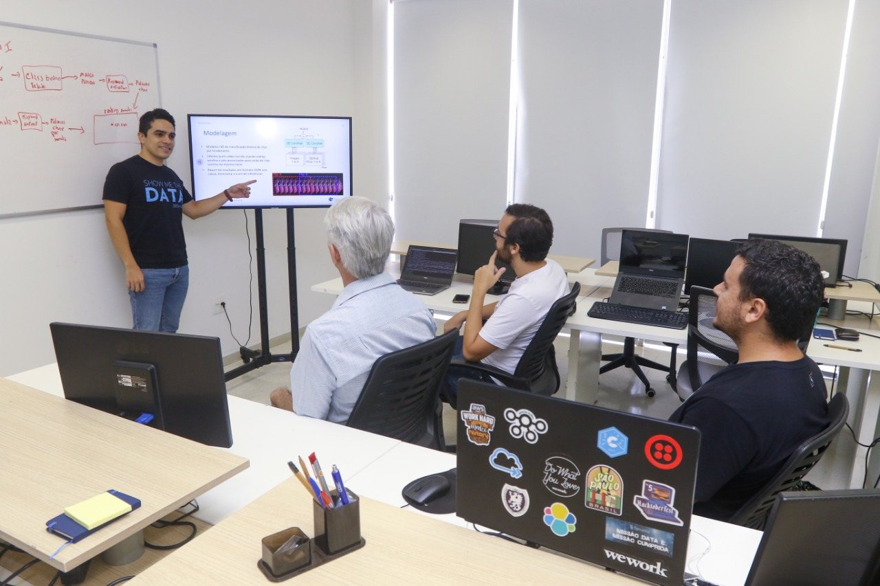 A foto foi tirada da sala da empresa Semantix com quatro profissionais da empresa. Um deles está à frente mostrando algum conteúdo em u painel digital. Os demais estão sentados olhando a explicação.