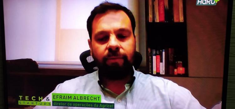 Na imagem está o diretor de operações da startup Agricef, Efraim Albrecht, em uma tela de televisão vestindo uma camisa polo na cor branca.