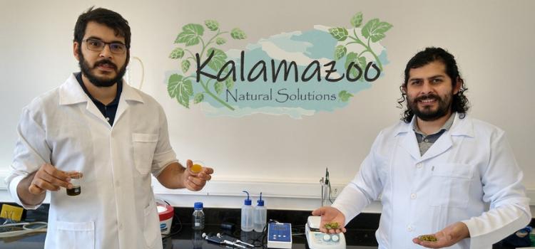 Da esquerda para a direita está Aureliano Dias vestindo um jaleco branco e Manuel Barrales usando também um jaleco branco. Eles estão no laboratório da Kalamazoo, empresa-filha da Unicamp, mostrando os produtos de lúpulo que estão em desenvolvimento.