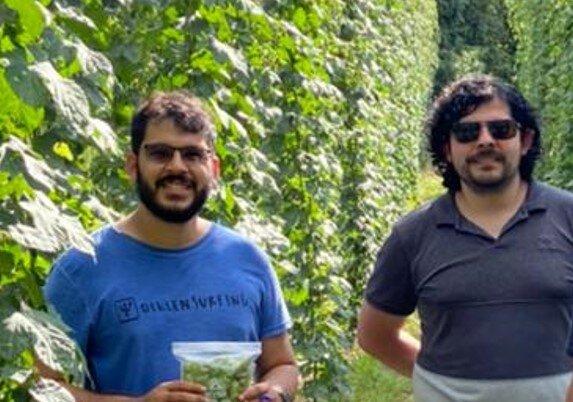 Aureliano Dias vestindo uma camiseta azul ao lado de Manuel Barrales que veste uma camiseta na cor escura. Eles estão em um campo de lúpulo de um de seus clientes.