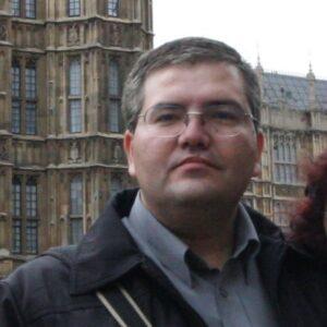 Homem, cabelos grisalhos, usa óculos